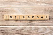 Influencer Word Written On Wood Block. Influencer Text On Table, Concept. poster