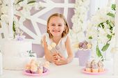 Little smiling blond girl holding colorful sweet lollipops on the background of pretty decorated can poster