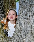 Young Girl Climbing in Tree smiling huge with Missing Front Teeth