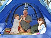 Father and Kids outdoors camping in dome tent