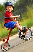 Cute young boy wearing safety helmet riding tricycle