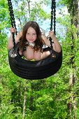 stock photo of tire swing  - Young girl at outside park swinging on tire swing - JPG