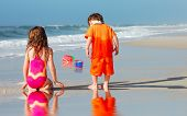 Young girl and boy playing on pretty beach