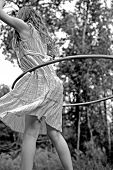 Young girl playing with hula hoop outdoors