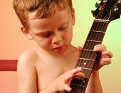 Young boy playing around with guitar instrument