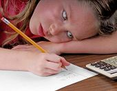 Young girl with head on desk working on math problems