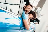 Man With Kid Are Sitting At The Wheel Of New Vehicle. Smiling Family. Car Buying In A Showroom. Auto poster