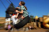 Young kids having fun on tire swing