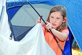 young girl out camping learning how to pitch tent