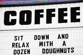 sign for coffee shop suggesting patrons eat a dozen donuts