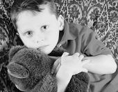 Young boy on retro couch with stuffed bear