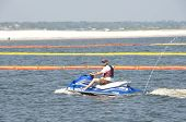 ORANGE BEACH, AL- JUNE 8: A recreational boater motors past protective oil boom positioned in Perdid