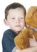 Tough young boy cuddling bear
