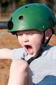 child riding trike wearing helmet