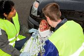 Paramedics helping a young injured victim of a car accident