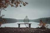 A Transparent Man Is Sitting On A Bench And Looking At The Lake. Back View. Autumn Theme poster
