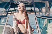 A Luxurious Attractive Woman In Summer Clothes And Sunglasses Swims By The Sea On Her Yacht, Enjoys  poster