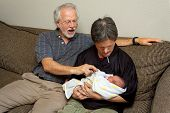 The White Haired Grandfather Of A Newborn Baby Helps His Brother-in-law With Downs Syndrome Hold The poster