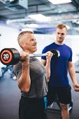Senior man weightlifting, assisted by personal trainer. Retirement activities. Fit lifestyle. poster