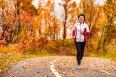 Middle age active and healthy Asian woman exercising weight loss body workout jogging running in par poster