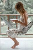 Woman in summer dress sits in the hammock in a garden and reads the book poster