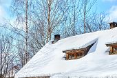 Roof Of A Low-rise Wooden Village House With Windows Under The Snow. Winter. Trees And Blue Sky With poster