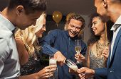 Young man pouring champagne in glasses for new year eve party. Happy and smiling girls and guys cele poster