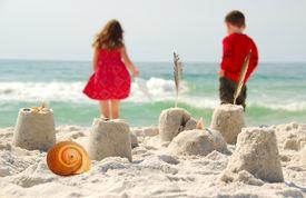 stock photo of children playing  - Young children playing at seashore - JPG