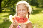 Beautiful Blonde Girl With Pigtails Eating A Watermelon