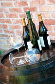 picture of wine cellar  - glasses and bottle of wine lying over wooden barrel - JPG