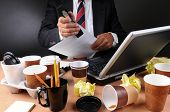 Closeup view of a very cluttered businessmans desk. Man is stapling papers with coffee cups and crum