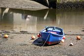 Generic rowing boat at low tide. All identifying marks removed.