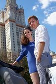 Young smiling couple stands on background of blue sky near to Lomonosov Moscow State University main