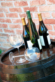 stock photo of wine cellar  - glasses and bottle of wine lying over wooden barrel - JPG
