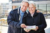 Two happy seniors on city trip with map