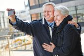 Happy senior couple taking pictures of themselves with a smartphone