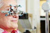 Senior woman with trial frame at optician for lens determination