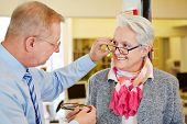 Optician offering consultation to senior woman for new glasses