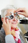 Optician adjusting the trial frame for a senior woman