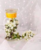 Flowering branches in glass bank on light fabric background