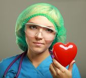 Female doctor with stethoscope holding heart, isolated on grey background