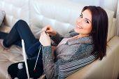 Jonge vrouw een sjaal breien en glimlachen