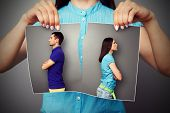 stock photo of love hurts  - woman lacerating photo of young couple in quarrel over dark background - JPG