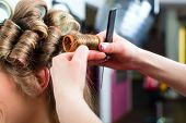 Hairdresser - hair stylist curling hairs, a female customer gets a haircut