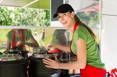 stock photo of ladle  - Female owner of a soup kitchen or a field kitchen stirs with a ladle in the soup - JPG