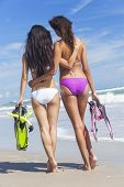 Rear view of two beautiful young women in bikinis with snorkel, mask & flippers embracing on a deser