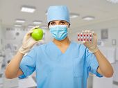 Doctor with pills and apple at medical office