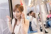 Asian beauty in MRT carriages use her cellphone, Taipei, Taiwan.