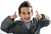 Portrait of a cute little boy smiling on white background holding thumbs up