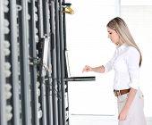 Empresaria joven ingeniera con portátil moderno en la sala de servidores de red